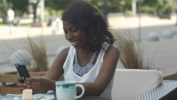 Thumbnail for African American Woman Using Phone, While Sitting in Outside Cafe