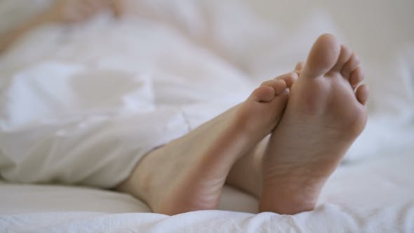 Thumbnail for Delicate Female Feet Moving Toes Playfully on White Bedding