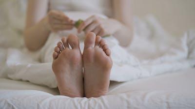 Woman Applying Cosmetic Foot Cream Doing Feet Massage