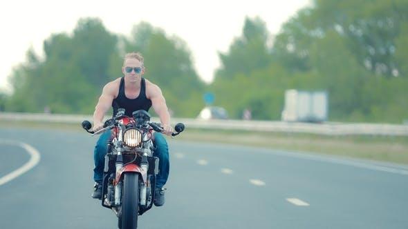 Biker Rides a Motorcycle on an Asphalt Road