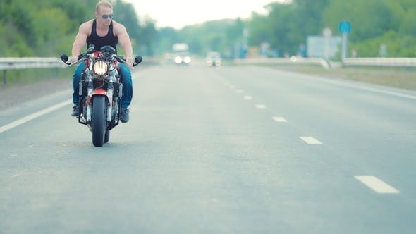 Young Macho Biker Rides Motorcycle on Highway in Sunglasses