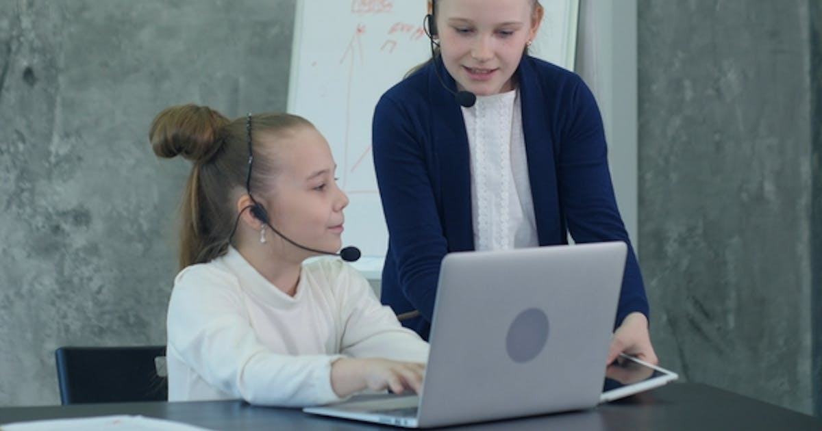 Pretty Two Little Girl in Headset Using Laptop and Flipchart in Office