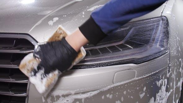 Ein Mann wäscht Autoscheinwerfer. Konzept der manuellen Autowäsche