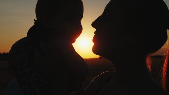 Silhouette of Mother with Baby at Sunset