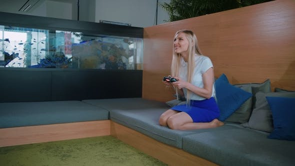 Thumbnail for Woman Gaming and Relaxing in Modern Office. Young Formal Woman in Skirt Chilling on Sofa in