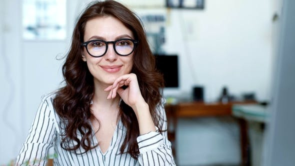 Thumbnail for Portrait Shot of Woman Looking at the Camera and Smiling While Working
