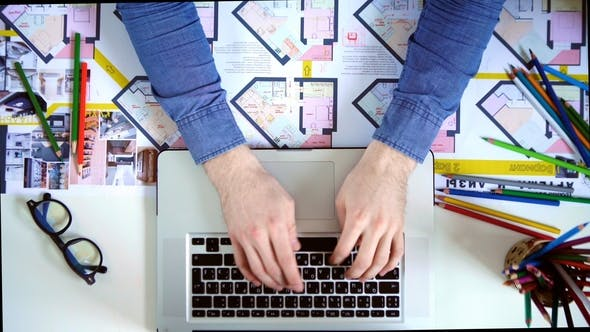 Thumbnail for Top View of Desk with Office Supplies. Man Typing on His Laptop