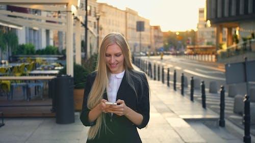 Formal Business Woman Walking on Street. Elegant Blond Woman in Suit and Walking on Street and