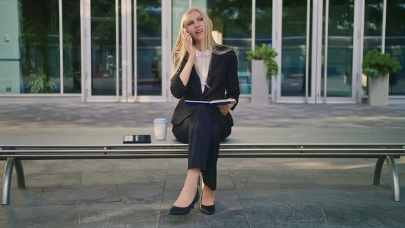 Thumbnail for Woman with Notepad Speaking on Phone Outdoors. Modern Business Woman in Suit Sitting on Bench with