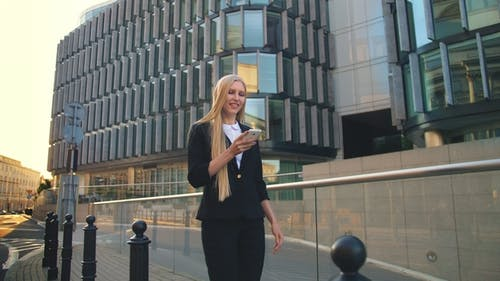 Modern Woman Walking on Contemporary Urban Street. Business Woman Using Phone and Walking on Paved