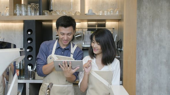 Thumbnail for Portrait of Two Asian Barista Using Tablet at the Work Day in the Coffee Shop and Smiling on Camera.