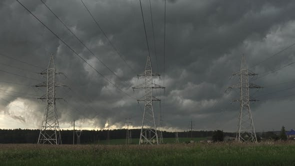 Thumbnail for Dark Clouds Float Across Sky Against Electric Power Pylons of Transmission Line
