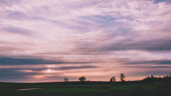 Thumbnail for A Magnificent Sunset Over a Field with Pink Hues on the Clouds