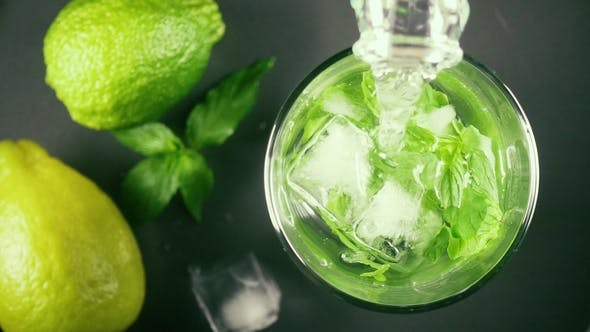 Thumbnail for Water From a Bottle in a Glass of Mint and Ice Top View