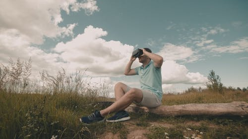 Man in Virtual Reality Headset Sitting at Nature. Male Watching Video 360
