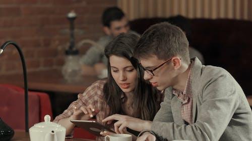 Couple Using Digital Tablet and Smoking Hookah in Shisha Cafe