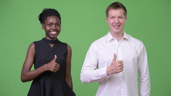 Cover Image for Two Young Multi-ethnic Business Couple Giving Thumbs Up Together