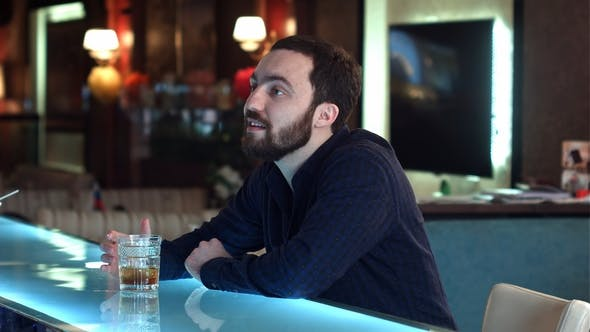 Thumbnail for Young Man in a Bar Having a Conversation with Bartender and Drinking