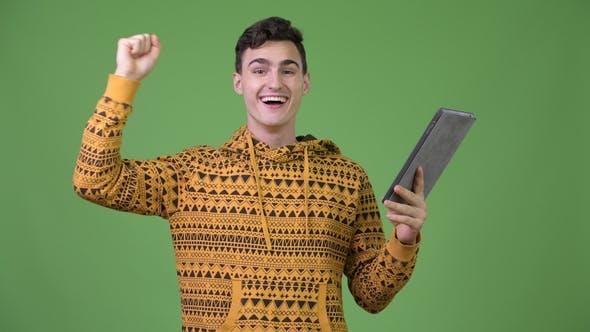 Cover Image for Junge gutaussehende Mann mit digitalen Tablet und immer gute Nachrichten