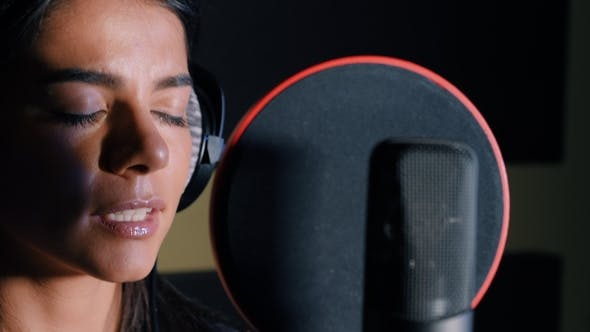 Cover Image for Young Beautiful Brunette Woman Recording Voice, Song or Album in Professional Studio. Girl Sings
