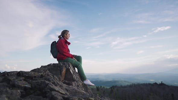 Thumbnail for Portrait of a Girl Traveler in the Mountains. Young Woman Tourist Sitting Resting on the Rocks at
