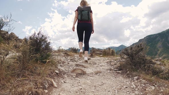 Thumbnail for Girl Walks Along a Path in a Rocky Terrain. Young Woman Tourist with a Backpack