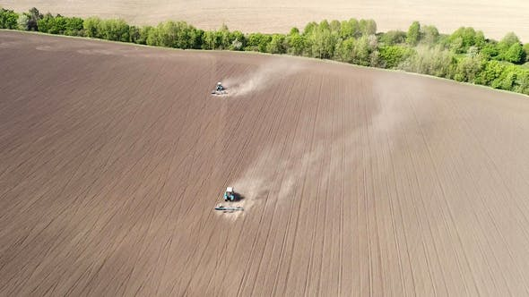 Aerial View of Agricultural Tractors Cultivating Field.