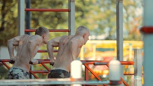 Zwei junge Athleten machen Liegestütze an den Bars