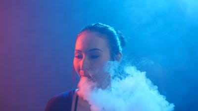 Night Life Concept. Young Woman Smokes Electronic Cigarette in Color Light