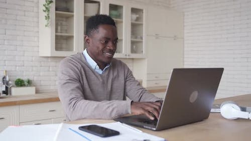 Smiling African American Man Using Laptop Computer Working From Home Office