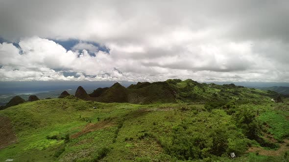 Aerial view of peak Chocolate hills and cloudy sky in Badian, Philippines.