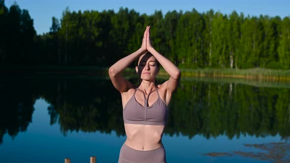 Thumbnail for Beautiful Young Woman Performing a Spiritual Yoga Pose on a Forest Lake at Sunny Day, Sunrise Zen