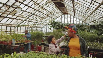 Afro-American Boy Hugging Mother in Greenhouse