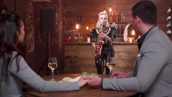 Thumbnail for Female Musician Performing a Romantic Song for a Couple in a Restaurant