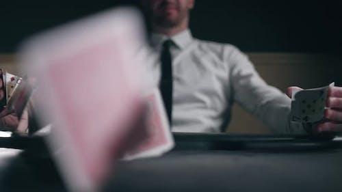Ein professioneller Croupier arbeitet und mischt mit Karten
