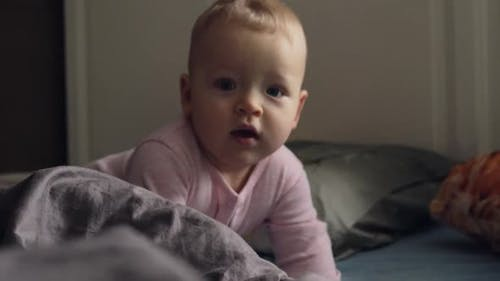 A Baby Girl in Pink Romper Suit on a Messy Bed