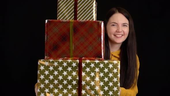 Cover Image for Junge Frau mit Geschenkbox auf schwarzem Hintergrund, Geschenkbox mit weißem Band für ein glückliches neues Jahr