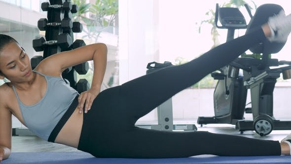 Thumbnail for Beautiful Woman Doing a Workout Lying on Her Side on the Floor with Her Leg Raised in the Air To