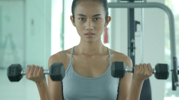 Thumbnail for Attractive Shape Young Sporty Focused Fitness Asian Girl with Ponytail Doing Biceps Exercises While