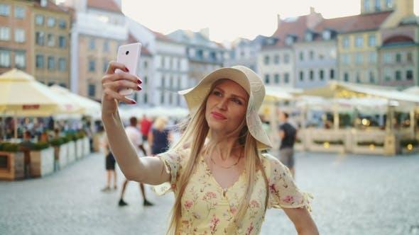 Thumbnail for Frau nimmt Selfie auf Platz. Attraktive Frau posiert für Selfie und steht auf dem Stadtplatz.