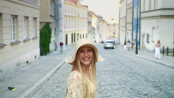 Thumbnail for Smiling Woman Walking on Street. Cheerful Pretty Woman in White Hat Looking Back at Camera While