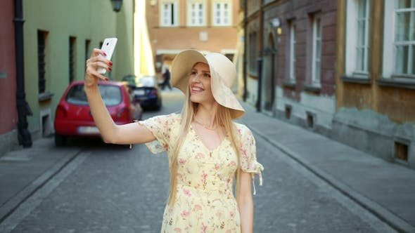 Thumbnail for Woman Taking Selfie on Street. Cheerful Young Woman Walking on Old European Town Street and Taking