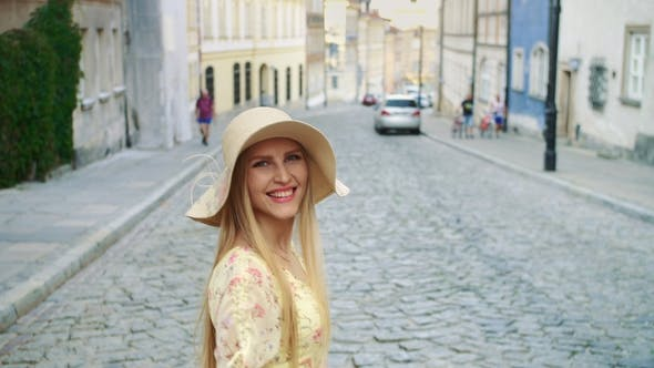 Thumbnail for Smiling Woman Walking on Street. Cheerful Pretty Woman in White Hat Looking Back at Camera
