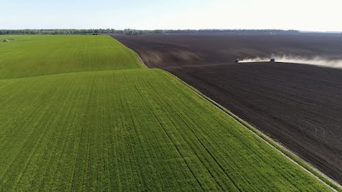 Aerial View of Agricultural Tractors Cultivating Field