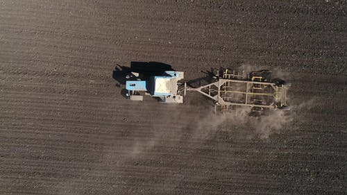 Aerial View of Agricultural Tractor Cultivating Field