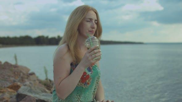 Entspannte Frau genießen Mojito Cocktail am Meer