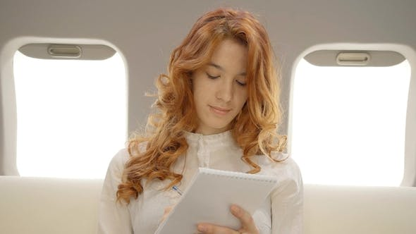 Thumbnail for Businesswoman Working on Business Plan in Private Aircraft.