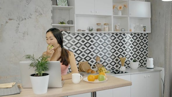 Thumbnail for Young Woman Eating Apple, Sitting at Table with Laptop in Home Kitchen.