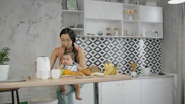 Thumbnail for Young Asian Mother Holding Little Baby on the Knees, Sitting in the Kitchen.