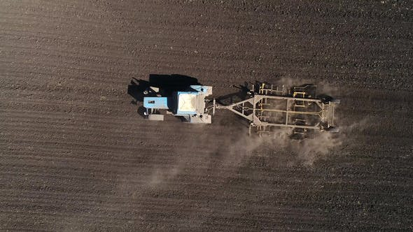 Aerial View of Agricultural Tractor Cultivating Field. Tractor At Work.